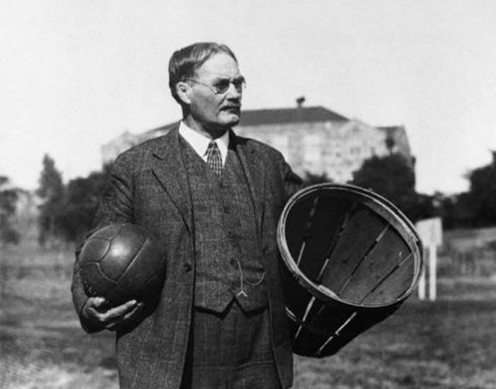 James Naismith, the inventor of basketball, with a basketball and a basket in the early days of the sport